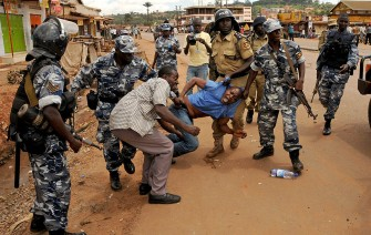 Uganda Police detain a protester, Thursday, April 14, 2011 in Kampala, Uganda. Witnesses in Uganda say police fired tear gas into a hospital during a skirmish with stone-throwing protesters. Military police officers shot Uganda's top opposition politician in the arm Thursday and fired tear gas into a hospital as demonstrations against rising fuel and food prices broke out in several locations across the country, officials said. The opposition politician, Kizza Besigye, was walking to work to protest high gas prices (AP Photo/Stephen Wandera)
